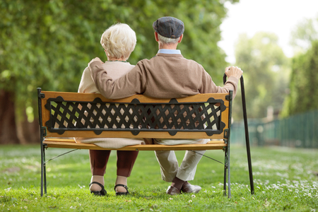 Rear view shot of a senior couple sitting on a wooden bench in the park 版權商用圖片