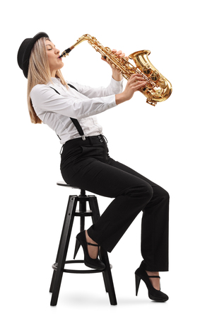 Woman sitting on a chair and playing a saxophone isolated on white background