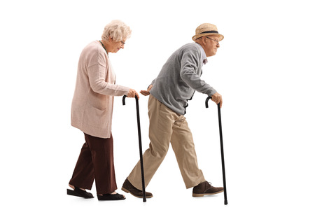 Full length profile shot of an elderly man and an elderly woman with canes walking isolated on white background