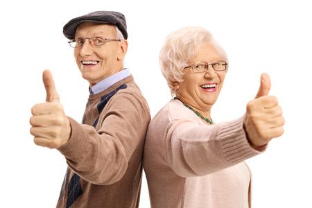 Seniors alegres sosteniendo sus pulgares para arriba aislados en el fondo blanco Foto de archivo - 79145618