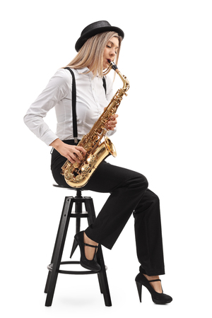 Female jazz musician seated on a chair playing a saxophone isolated on white background Stock Photo