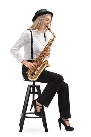 Vrouwelijke jazzmuzikant zittend op een stoel die een saxofoon speelt die op een witte achtergrond wordt geïsoleerd Stockfoto