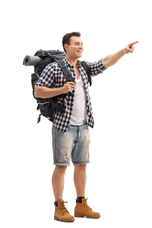 Full length portrait of a hiker pointing with his finger isolated on white background