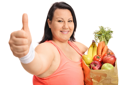 Happy woman making a thumb up gesture and holding a paper bag filled with fruit and vegetables isolated on white background
