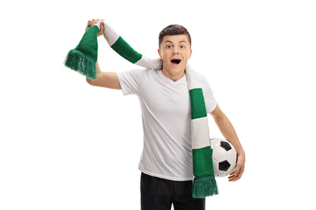Overjoyed teenage soccer fan with a scarf and a football isolated on white background