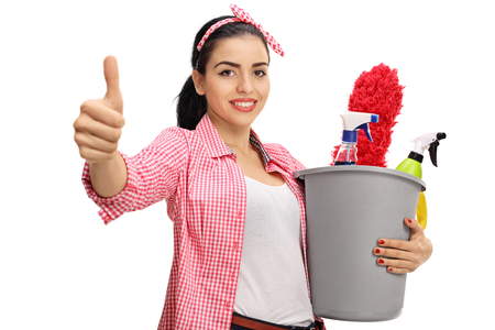 Young woman holding a bucket with cleaning products making a thumb up sign isolated on white background Stock Photo