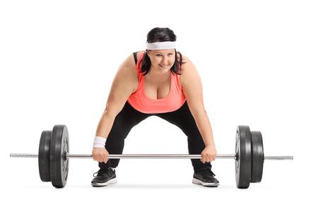 太りすぎの女性は、白い背景で隔離のバーベルを持ち上げる準備