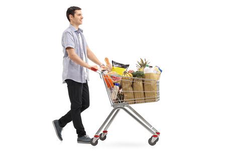 Full length profiel shot van een jonge man die een boodschappenwagentje vol met boodschappentassen drukt die op een witte achtergrond worden geduwd