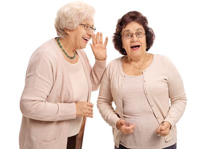 Mujer madura susurrando a su amigo sorprendido aisladas sobre fondo blanco Foto de archivo