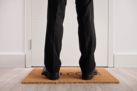 Person standing on a doormat with the word welcome written on it in front of a closed door Stock Photo