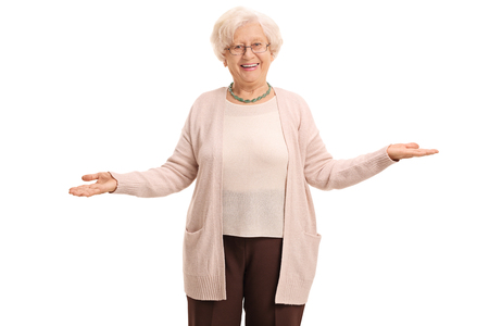 Cheerful elderly woman gesturing with her hands and looking at the camera isolated on white background