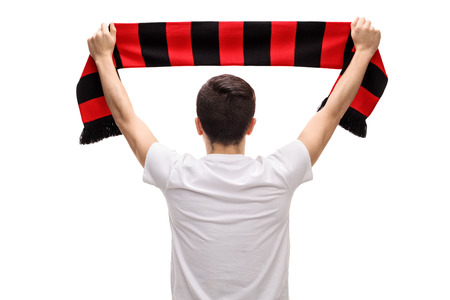 Rear view shot of a teenage soccer fan holding a scarf isolated on white background Archivio Fotografico