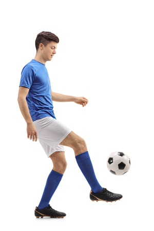 Full length profile shot of  a teenage soccer player juggling a football isolated on white background