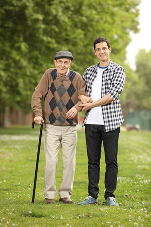 Full length portrait of a grandson helping his grandfather in the park Stock Photo