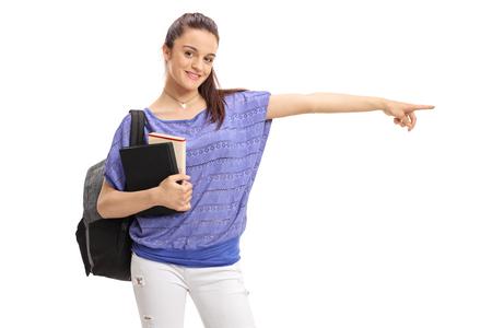 白い背景に分離された右指している本バックパックと 10 代の女子学生 写真素材