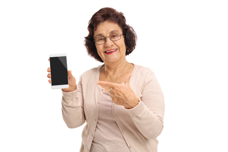 Elderly woman holding a phone and pointing isolated on white background
