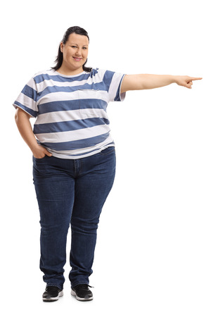 Full length portrait of a woman pointing right and looking at the camera isolated on white background Stock Photo