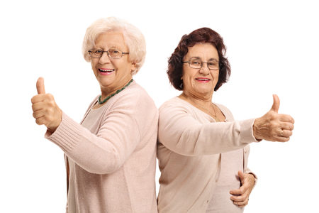 Two cheerful mature women holding their thumbs up and looking at the camera isolated on white background