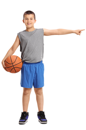 Full length portrait of a boy with a basketball pointing right isolated on white background