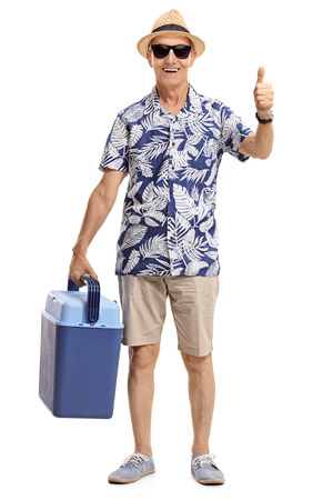 Full length portrait of a mature tourist with a cooling box making a thumb up gesture isolated on white background Stock Photo