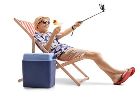 サンラウン ジャーでカクテル座って、白い背景で隔離 selfie を取って幸せな高齢者の観光客 写真素材