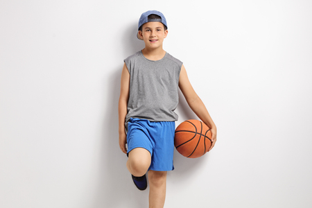 Boy with a basketball leaning against a wall photo