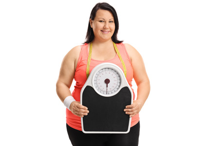 fatness: Overweight woman holding a weight scale and looking at the camera isolated on white background Stock Photo