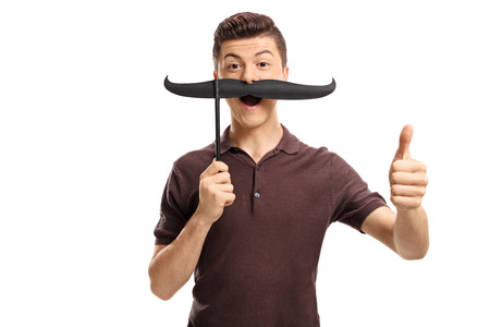 Teenage boy with fake moustache making a thumb up gesture isolated on white background Stock Photo
