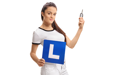 Teenage girl holding a car key and an L-sign isolated on white background Zdjęcie Seryjne