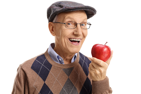 Cheerful senior having an apple isolated on white background Stockfoto