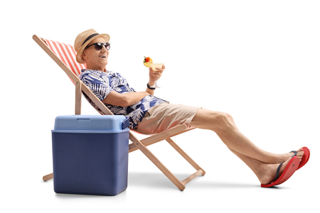 Elderly tourist with a cocktail sitting in a deck chair next to a cooling box isolated on white background Foto de archivo