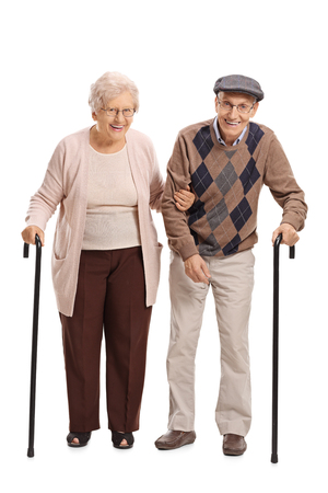Full length portrait of an elderly couple with canes looking at the camera and smiling isolated on white background