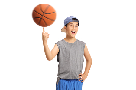 Joyful boy spinning a basketball on his finger isolated on white background photo