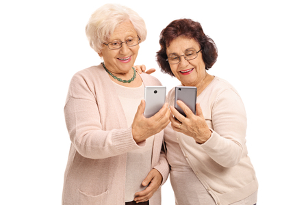immersed: Two elderly women looking at phones isolated on white background Stock Photo