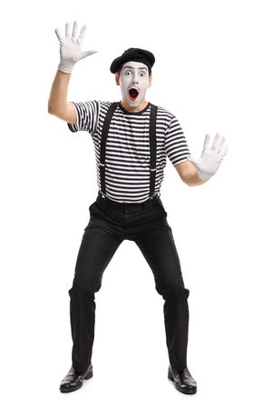 Full length portrait of a mime holding his hands on an invisible wall isolated on white background Archivio Fotografico