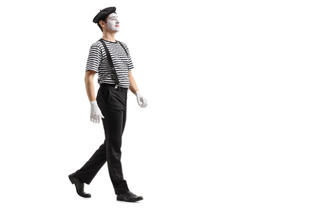 Full length profile shot of a mime walking isolated on white background