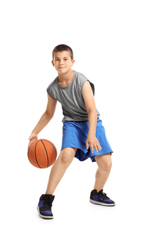 Full length portrait of a kid playing with a basketball isolated on white background