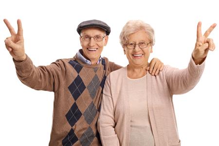 70s: Joyful senior couple making victory signs isolated on white background Stock Photo
