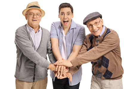 Young guy and two mature men putting their hands together and looking at the camera isolated on white background Stock Photo