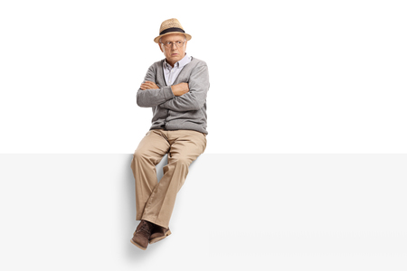 Angry senior sitting on a panel isolated on white background Stock Photo