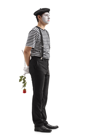 Full length profile shot of a sad mime with a rose waiting in line isolated on white background Stock Photo