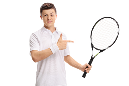 Teenage tennis player holding a racket and pointing isolated on white background 版權商用圖片