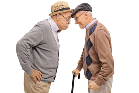 Furious seniors pushing their heads against each other isolated on white background
