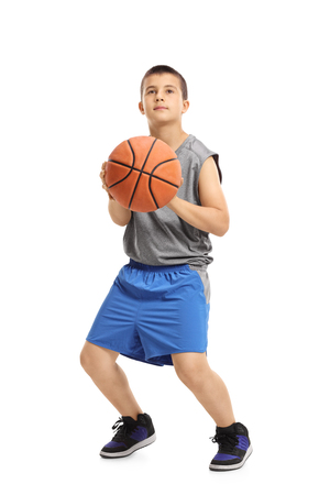Full length portrait of a boy about to throw a basketball isolated on white background photo