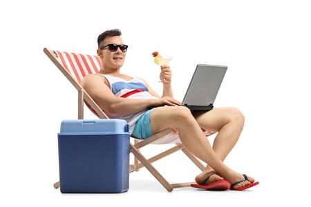 Jeune homme avec un ordinateur portable et un cocktail assis dans une chaise longue à côté d'une boîte de refroidissement isolé sur fond blanc Banque d'images - 81320022