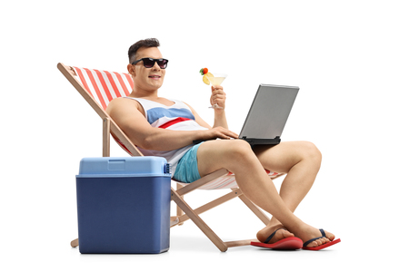 Young man with a laptop and a cocktail sitting in a deck chair next to a cooling box isolated on white background