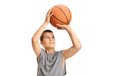 Boy throwing a basketball isolated on white background photo