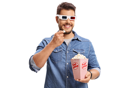 snacking: Man wearing a pair of 3D glasses and eating popcorn isolated on white background