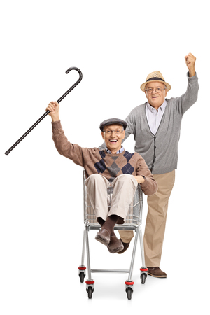 Joyful elderly man pushing another elderly man in a shopping cart isolated on white background
