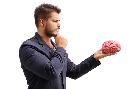 Pensive man looking at a brain model isolated on white background Stock Photo